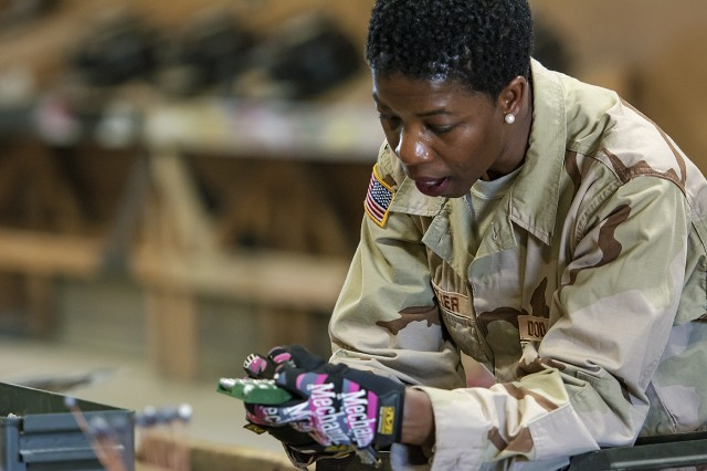 Christabel Frazier, quality assurance specialist, ammunition surveillance, Army Field Support Battalion-Afghanistan examines small arms ammunition during a periodic inspection at Bagram Airfield, Afghanistan, March 31. (U.S. Army Photo by Justin Graff, 401st AFSB Public Affairs)