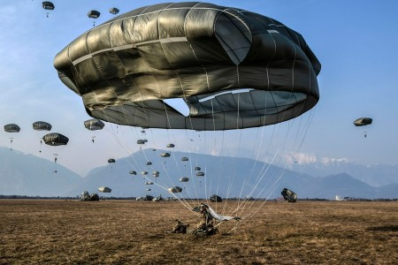 A paratrooper performs a parachute landing fall upon contact with the ground as the 173rd Airborne Brigade conducts an airborne assault in northern Italy, March 1, 2018.
