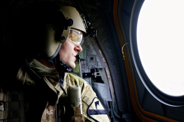 Sgt. Shane Outlaw, a CH-47 Chinook helicopter crewmember assigned to Company B, 2nd General Support Aviation Battalion, 227th Aviation Regiment, 1st Combat Aviation Brigade, 1st Cavalry Division, looks out over the Hohenfels Training Area in Germany during a local area orientation flight, Jan 16, 2018. Aviators of the battalion are familiarizing themselves with the training area to be prepared for the support they will provide during the upcoming Allied Spirit VIII exercise. (U.S. Army photo by Sgt. Gregory T. Summers / 22nd Mobile Public Affairs Detachment)