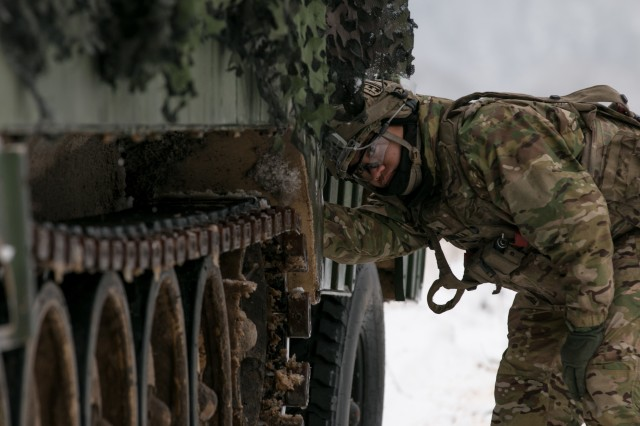 Sgt. Antonio Bornilla, a firing control specialist with Battery C, 1st Battalion, 7th Field Artillery Regiment, 2nd Armored Brigade Combat Team, 1st Infantry Division, Fort Riley, Kansas, inspects the track on his vehicle during training at Hohenfels, Germany Jan. 22, 2018. Bornilla is among 4,100 troops from 10 nations participating in Allied Spirit VIII, a multinational training exercise designed to test participants' readiness and capabilities. (U.S. Army photo by Spc. Dustin D. Biven / 22nd Mobile Public Affairs Detachment)