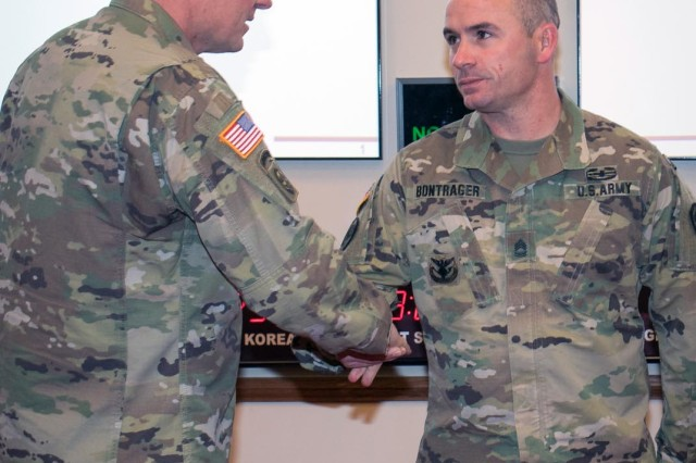 Maj. Gen. Wilson A. Shoffner, FCoE and Fort Sill commanding general, presents his coin of excellence to Sgt. 1st Class Gregory Bontrager, 428th FA Brigade, March 29, 2018, at McNair Hall. Bontrager was honored as the TRADOC Career Counselor of the Year.