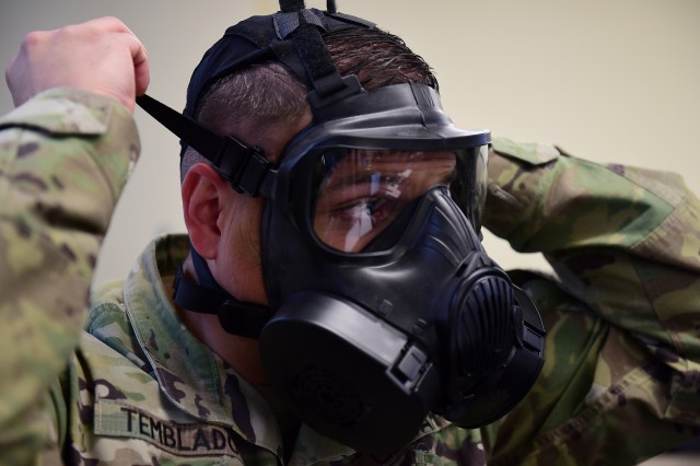 Staff Sgt. Eliud Temblador, Regional Contracting Center-North NCO in charge of contracting, dons his gas mask during a joint training exercise simulated attack March 21, 2018, at Fort Bragg, North Carolina. The team faced numerous incursions during the exercise, such as being under attack, and had to continue to execute its contingency contracting mission.
