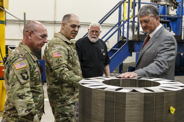 Chris Williams, right, chief of the Turbine Drive Train Division, and Leonard Farrar, a machining leader, showcase the resistance welding capabilities performed at Anniston Army Depot to Gen. Gus Perna, second from left, commanding general of Army Materiel Command, and ANAD Commander Col. Joel Warhurst.
