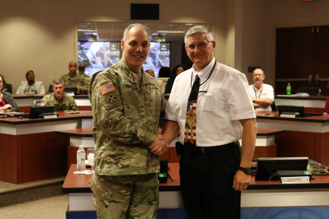 Army Materiel Command's Commander Gen. Gus Perna presents a recognition coin to Lloyd Willits for his support to the Soldier.