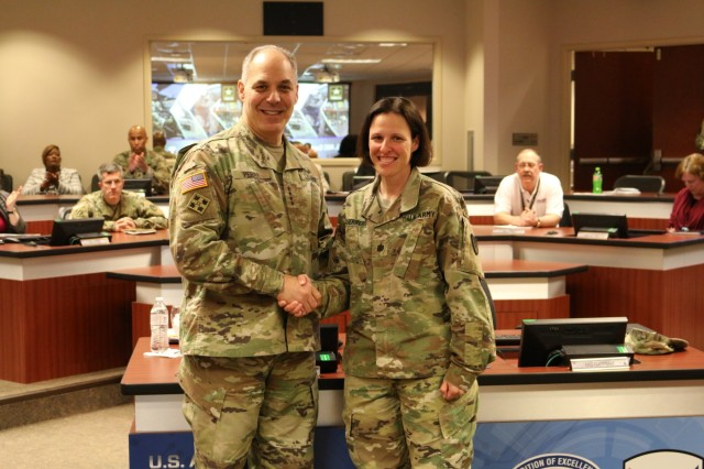 Army Materiel Command's Commander Gen. Gus Perna presents a recognition coin to Lt. Col. Jennifer Guerrero for her support to the Soldier.