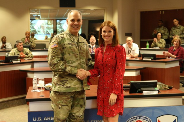 Army Materiel Command's Commander Gen. Gus Perna presents a recognition coin to Diana Daniel for her support to the Soldier.
