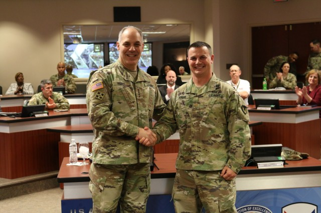 Army Materiel Command's Commander Gen. Gus Perna presents a recognition coin to Maj. Ryan Atkins for his support to the Soldier.
