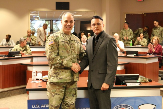 Army Materiel Command's Commander Gen. Gus Perna presents a recognition coin to Casey Jones for his support to the Soldier.