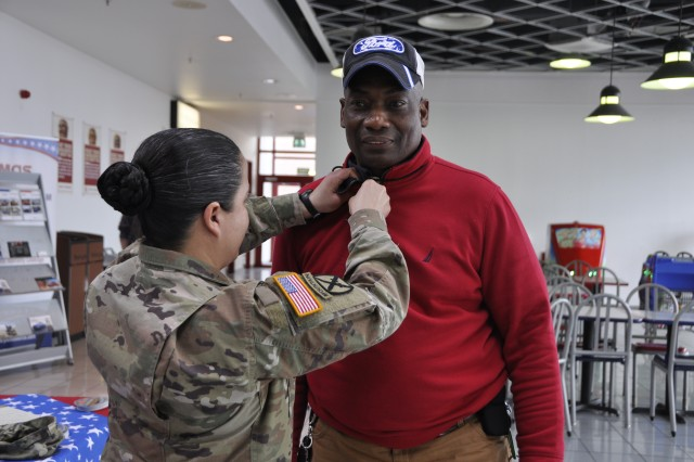Army Command Sgt. Maj. Samara Pitre, of U.S. Army Garrison Benelux, puts the Vietnam War Lapel Pin on Hillard Grimes, the general manager's courier at AAFES, March 29, 2018, on Chièvres Air Base, Belgium. Veterans were honored during National Vietnam War Veterans Day.