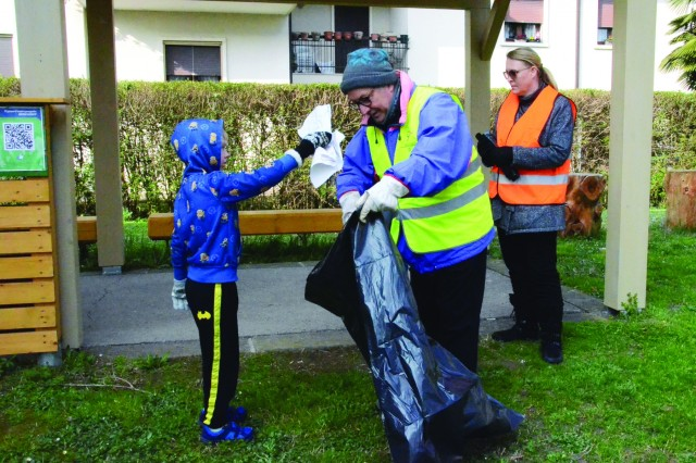 Bryson Strubinger, 6, throws a piece of paper in the plastic bag held by Albano Crivellaro, Alpino Gruppo Costozza during the March 24 cleanup day near Longare, Italy. Also pictured, Bryson's mother, Sgt. First Class Brandi McElyea of the 207th Military Intelligence Brigade.