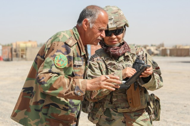 Master Sgt. Janet Bretado, logistics advisor for the Military Advisory Team, Train, Advise and Assist Command-South, shows a logistics Afghan officer a photo, March 27,2018, during a routine visit in Kandahar, Afghanistan. Bretado is one of two females from the 40th Infantry Division in TAAC-South, which is composed of Soldiers from the 40th Inf. Div., California National Guard, and 2nd Infantry Brigade Combat Team, 4th Infantry Division. (U.S. Army photo by Staff Sgt. Neysa Canfield/TAAC-South Public Affairs)