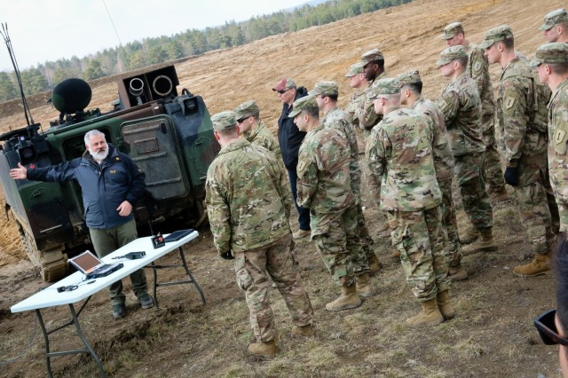 Ray Moldovan (left), a senior product management specialist with General Dynamics, explains to a group of U.S. Army Soldiers how to remotely control a M58 Wolf during a multinational joint equipment training exercise at Grafenwoehr Training Area, Germany, April 2, 2018, in preparation for a Robotic Complex Breach Concept demonstration.