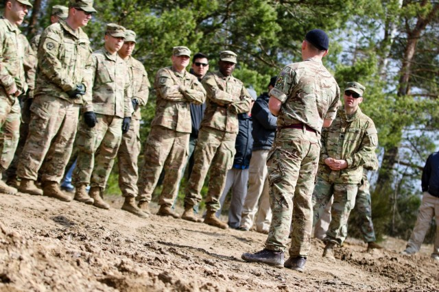 U.K. army Staff Sgt. Joe Ferries, a combat engineer with the 22nd Engineer Regiment, 8th Engineer Brigade, instructs a group of U.S. Soldiers, Marines, and Department of Defense civilians on how to remotely control a Terrier armored digger during a multinational joint equipment training exercise at Grafenwoehr Training Area, Germany, April 2, 2018, in preparation for a Robotic Complex Breach Concept demonstration.
