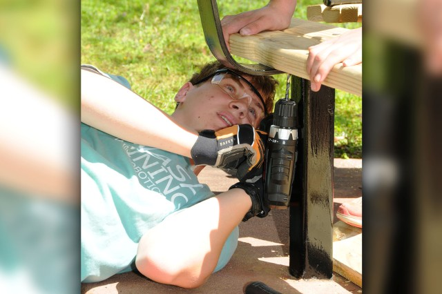 Justin Jahnke, Boy Scout with Troop 57, screws in boards to rebuild benches at the main post chapel's Military Spouse Memorial Garden as part of an Eagle Scout project March 29.