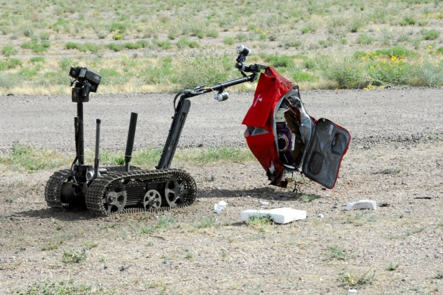 A TALON explosive ordnance disposal robot is remotely controlled by an EOD technician from the 71st Ordnance Group (EOD) to move a suspected exercise improvised explosive device to an area where it can be rendered safe at Pinal Air Park, Ariz. during Raven's Challenge XII, March 19-23. The Raven's Challenge Exercise is an annual, interagency, counter IED exercise that incorporates scenarios focused on interoperability capabilities between public safety bomb squads (PSBSs) and military EOD units in operational environments.