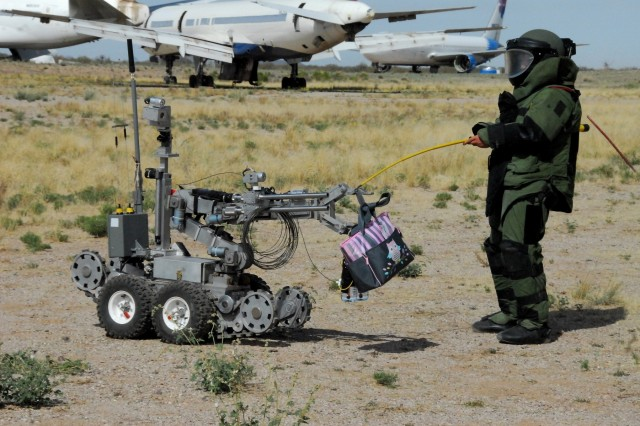 Staff Sgt. Michael Sprouse from San Diego, Calif., an explosive ordnance disposal team leader with the 741st Ordnance Company, 3rd Ord. Battalion., at Fort Bliss, Texas, passes off a suspected exercise improvised explosive device to an ANDROS EOD robot at Pinal Air Park, Ariz. during Raven's Challenge XII, March 19-23. The Raven's Challenge Exercise is an annual, interagency, counter IED exercise that incorporates scenarios focused on interoperability capabilities between public safety bomb squads (PSBSs) and military EOD units in operational environments.