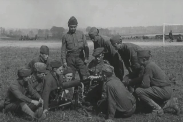 """Noncommissioned officers of the 77th Division's 304th Machine gun battalion receive instruction in operating the Vickers machine gun from British Army Sgt. D. Harris, a member of the 44th Machinegun Company of the 44th Battalion in May 1918 in this still from a 1918 silent movie , """"Training with the British Army in Picardy, May 1918"""" on the National Archive's wesbite. The 77th Division, composed of draftee Soldiers from New York City, was one of five American divisions which was trained by the British Army after arriving in France. ( U.S. Army photo by U.S. Army Signal Corps via National Archives)"""
