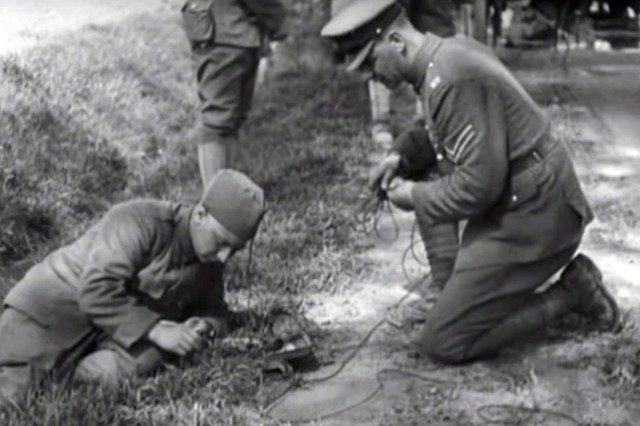 """Army Sgt. 1st Class Al H. Pfieffer, a member of the 77th Division, sends a message on a field phone under the watchfull eye of a British instructor, during training with the British Army in Picardy, France on May 15, 1918 in this still from the silent film """"Training with the British Army in Picardy, May 1918"""" on the National Archives website. The 77th Division, made up of draftees from New York City, was one of five American Army divisions to train with the British Army during World War 1. ( U.S. Army photo by U.S. Army Signal Corps via National Archives)"""