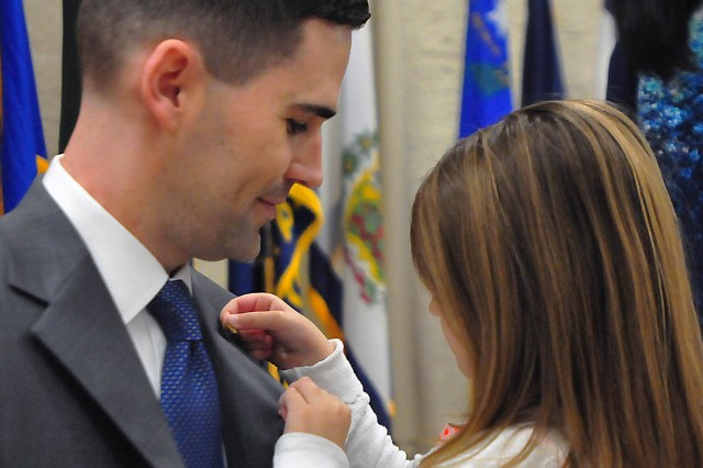 Kate Sannito places the Senior Executive Service lapel pin on her father, Matt Sannito, during his promotion ceremony into the Senior Executive Service, April 5 at Heritage Hall, Rock Island Arsenal, Illinois. Sannito is the executive director for Support Operations, ASC. (Photo by Jon Micheal Connor, ASC Public Affairs)