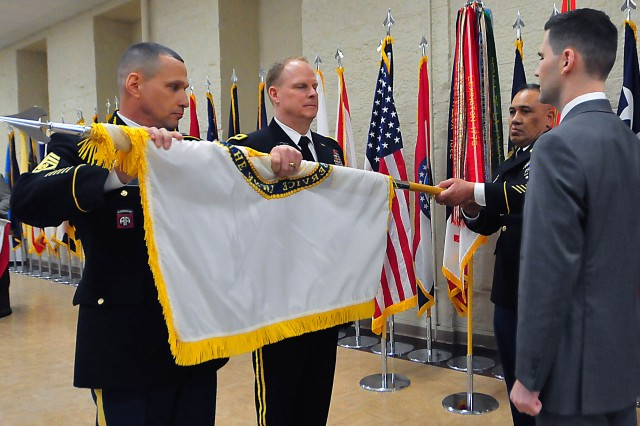 The U.S. Army Sustainment Command's Command Sgt. Maj. Joe Ulloth unfurls the Senior Executive Service flag presented to Matt Sannito during his SES promotion ceremony April 5 at Heritage Hall, Rock Island Arsenal, Illinois. (Photo by Jon Micheal Connor, ASC Public Affairs)