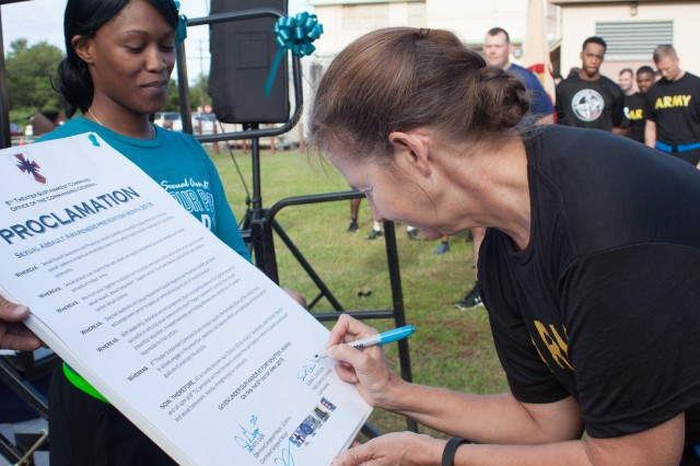 Maj. Gen. Susan A. Davidson, commanding general of the 8th Theater Sustainment Command, signs a proclamation officially recognizing April as Sexual Assault Awareness and Prevention Month April 6 during the SHARP fun run/walk at Fort Shafter. The proclamation called upon all 8th TSC personnel and their families to increase participation in efforts to prevent sexual assault and sexual harassment. (U.S. Army photo by Staff Sgt. John Portela)