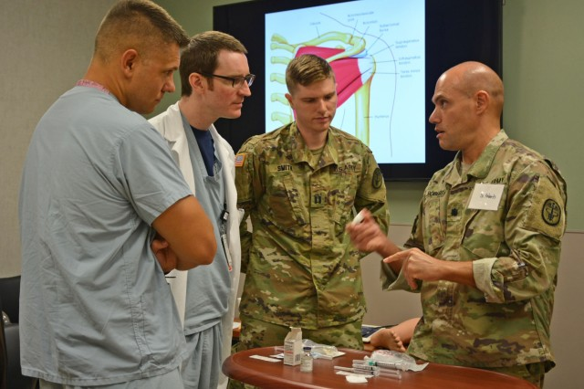"(Left-Right) Tripler Army Medical Center, TAMC, Resident Physicians Capt. Jon Stomer, Capt. Timothy Wulfestieg and Capt. Hunter Smith learn fundamentals in musculoskeletal medicine during the course, ""Simulation Training for Operational Medicine Providers,"" or STOMP course, from Lt. Col Jefferson Roberts, (right), director of the TAMC Medical Simulation Center and course instructor, Apr. 4, 2018, located at the TAMC Medical Simulation Center, Honolulu, Hawaii. The STOMP program at TAMC provides a necessary foundational knowledge base for the general medical officer as he/she prepares to provide medical support to soldiers and their chain of command in operational medicine and field environments. Specially designed for Army Medicine residents and interns, this simulation course offers participants an opportunity to meet with subject matter experts from the TAMC Emergency Department, Family Medicine, General Surgery, Musculoskeletal, Neurosurgery, Obstetrics & Gynecology, Operational Medicine, Orthopedics, and Urology Departments to learn, practice, and demonstrate patient care skills through the use of simulation training. The TAMC Medical Simulation Center uses multi-specialty simulation training to enhance graduate medical education programs ensuring residents are ""trained, competent, safe and ready"" to care for our soldiers and beneficiaries."