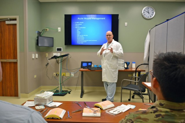"Col. Dwight Kellicut, chief of Vascular Surgery at Tripler Army Medical Center, or TAMC, discusses acute wound management techniques with residents, medical students and transitional year interns during the course, ""Simulation Training for Operational Medicine Providers,"" or STOMP course, at the TAMC Medical Simulation Center, Honolulu, Hawaii, Apr. 4, 2018. The STOMP program at TAMC provides a necessary foundational knowledge base for the general medical officer as he/she prepares to provide medical support to soldiers and their chain of command in operational medicine and field environments. Specially designed for Army Medicine residents and interns, this simulation course offers participants an opportunity to meet with subject matter experts from the TAMC Emergency Department, Family Medicine, General Surgery, Musculoskeletal, Neurosurgery, Obstetrics & Gynecology, Operational Medicine, Orthopedics, and Urology Departments to learn, practice, and demonstrate patient care skills through the use of simulation training. The TAMC Medical Simulation Center uses multi-specialty simulation training to enhance graduate medical education programs ensuring residents are ""trained, competent, safe and ready"" to care for our soldiers and beneficiaries."