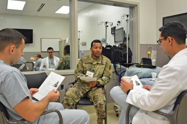 "Capt. McHuy McCoy, (center), staff physician at Tripler Army Medical Center, or TAMC, squadron flight surgeon at 2-6 Cavalry Squadron, 25th Combat Aviation Brigade, and co-facilitator of the course, ""Simulation Training for Operational Medicine Providers,"" discusses operational medicine with TAMC Resident Physicians Capt. Vladimir Fridkin, (left), and Capt. Joseph Gutierrez, (right), to prepare them to serve as general medical officers in operational and field environments upon completion of the TAMC residency or transitional year internship program. The STOMP program at TAMC provides a necessary foundational knowledge base for the general medical officer as he/she prepares to provide medical support to soldiers and their chain of command in operational medicine and field environments. Specially designed for Army Medicine residents and interns, this simulation course offers participants an opportunity to meet with subject matter experts from the TAMC Emergency Department, Family Medicine, General Surgery, Musculoskeletal, Neurosurgery, Obstetrics & Gynecology, Operational Medicine, Orthopedics, and Urology Departments to learn, practice, and demonstrate patient care skills through the use of simulation training. The TAMC Medical Simulation Center uses multi-specialty simulation training to enhance graduate medical education programs ensuring residents are ""trained, competent, safe and ready"" to care for our soldiers and beneficiaries."