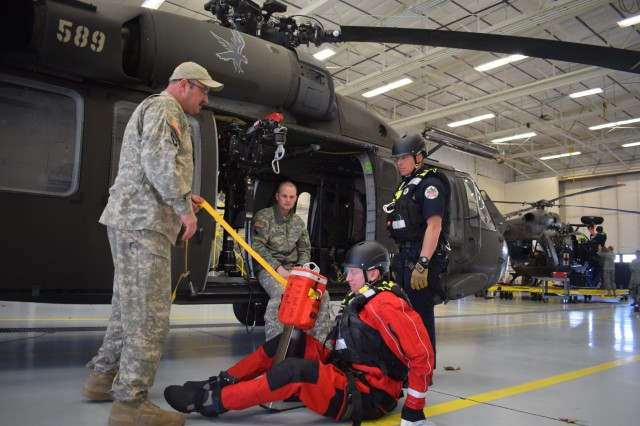 Sgt. 1st Class Tyler Bramble instructs a member of the Boise Fire Department on hoist operations April 3, 2018, at Gowen Field, Boise, Idaho. Bramble was the lead UH-60 instructor during the three-day training event with the Boise Fire Department's dive/swift water rescue team.
