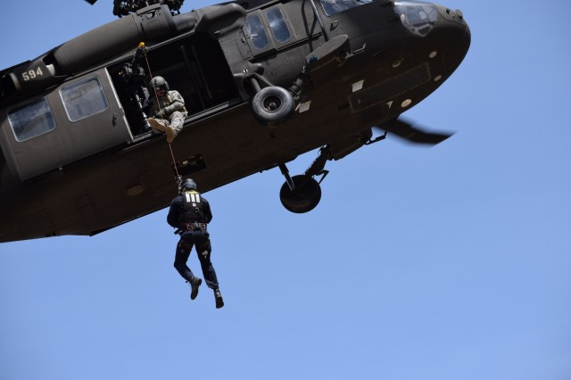 A member of the Boise Fire Department's dive/swift water rescue team trains April 3, 2018, on the Idaho Army National Guard's UH-60 hoist to prepare the organizations to work together on future domestic operations.