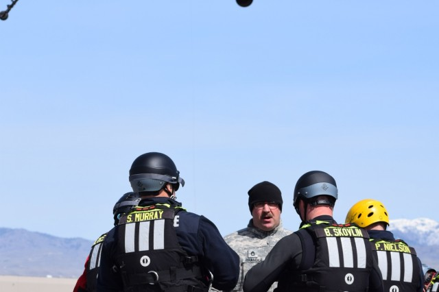 Sgt. 1st Class Tyler Bramble instructs member of the Boise Fire Department on hoist operations April 3, 2018, at Gowen Field, Boise, Idaho. Bramble was the lead UH-60 instructor during the three-day training event with the Boise Fire Department's dive/swift water rescue team.