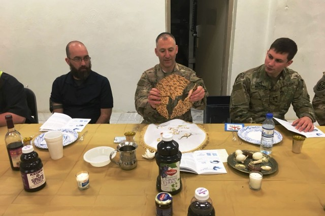 Maj. Johnathan Zagdanski (center), 361st Civil Affairs Brigade chaplain, breaks matza, unleavened flatbread, during a Passover Seder with Soldiers and civilians at Bagram Air Field, Afghanistan, March 30. (Courtesy photo)