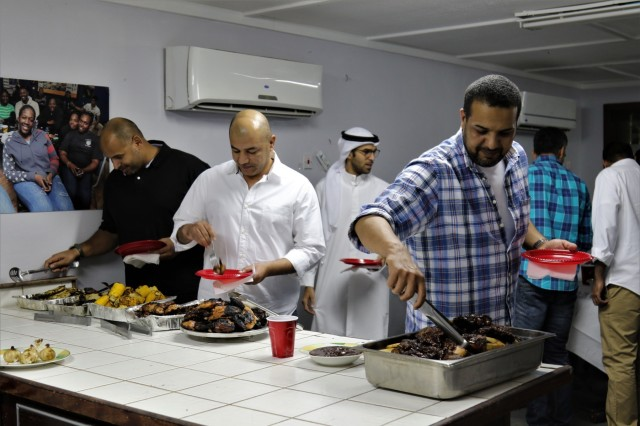 Kuwaiti Land Forces soldiers load up plates to enjoy a barbecue and social event hosted by 35th Inf. Div. at Camp Arifjan, Kuwait, Nov. 1, 2017. The purpose of the dinner was for the Kuwaiti Land Forces and 35th Inf. Div. to enjoy one another's company in a social setting and have an opportunity to become better acquainted in a relaxed atmosphere.