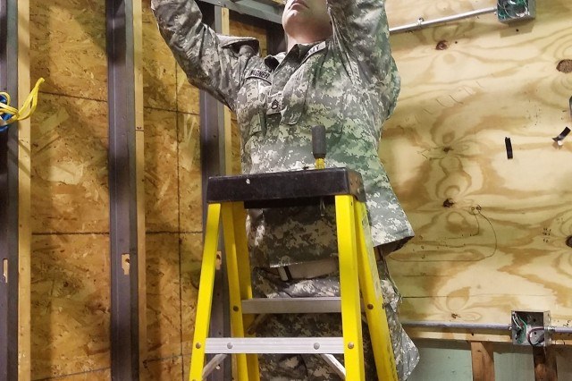 An Army Reserve Soldier installs a light fixture during the 12R Interior Electrician course taught by instructors from the 80th Training Command and 102nd Training Division (Maneuver Support) at The Army School System Training Center Dix, New Jersey, March 29, 2018.