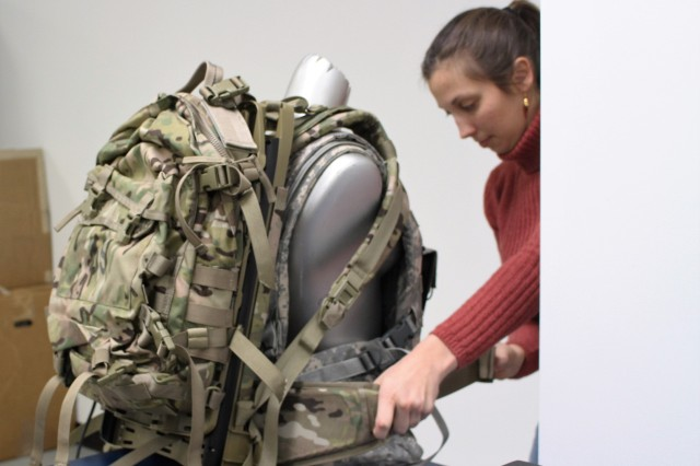Julie Douglas, CERDEC CP&ID engineer, adjusts the Energy Harvesting Assault Pack. With each step a Soldier takes, the rucksack glides up and down while the generator captures small amounts of kinetic energy and converts it into usable electrical energy.