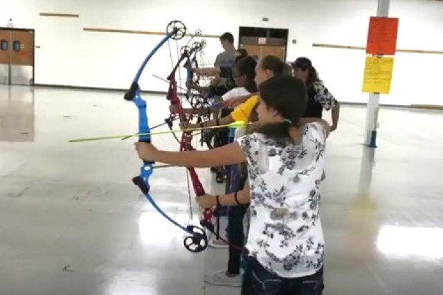 Students at the SKIES Unlimited Archery Academy prepare for shooting practice at the 10 meter line.