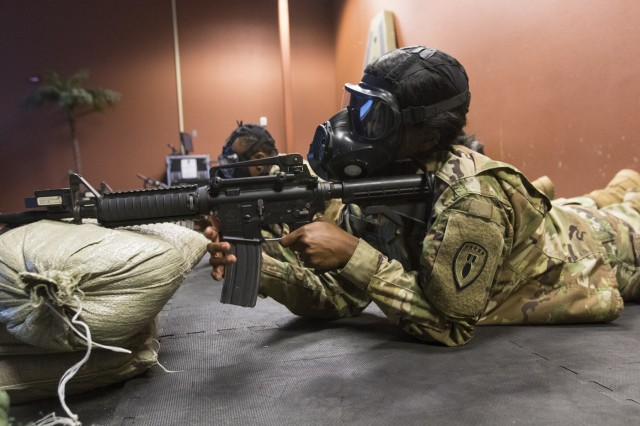 Spc. Ymonie Gill, a human resources specialist with Headquarters and Headquarters Detachment, 71st Ordnance Group (EOD), performs a rifle marksmanship simulated qualification at an Engagement Skills Trainer (EST) facility, while wearing a M50 Joint Service General Purpose Mask, known as the pro-mask, during the detachment's (CBRN) training week, Mar. 21-23, 2018, at various locations on Fort Carson, Colo. More than 50 other 71st EOD Soldiers participated in the training, which also served as an exercise in familiarization of current CBRN prevention techniques and procedures. (U.S. Army photo by Staff Sgt. Lance Pounds, 71st Ordnance Group (EOD), Public Affairs)