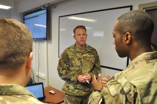 Maj. John Cross talks about refining contracting products with other contracting Soldiers April 4, 2018, at Fort Bragg, North Carolina. Cross is a contracting officer from the 900th Contracting Battalion at Fort Bragg.