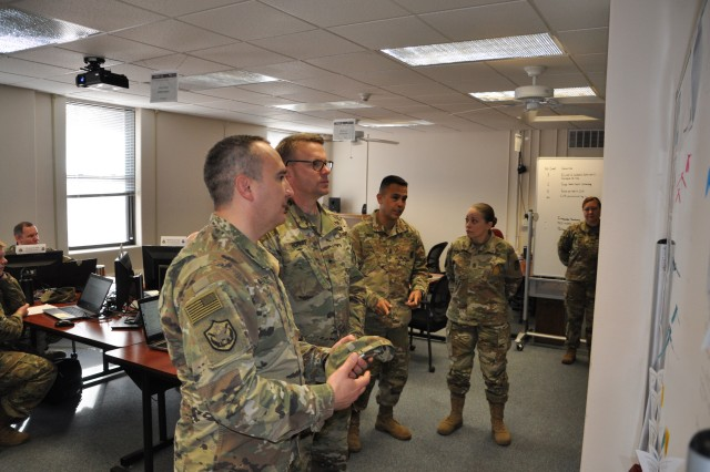 Lt. Col. Tom McFall and Sgt. Maj. Sol NevarezBerrios brief Brig. Gen. Bill Boruff and Command Sgt. Maj. Marco Torres on the 918th Contracting Battalion's preparations for Operational Contract Support Joint Exercise 2018 April 5, 2018, at Fort Carson, Colorado. McFall is the 918th CBN commander and NevarezBerrios is the Battalion sergeant major. Boruff is the commanding general of the Mission and Installation Contracting Command, and Torres is the MICC command sergeant major.