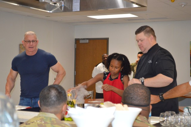 Taylor Flagg (center) assists chef's Robert Irvine and Shane Cash during a cooking demonstration at the teaching kitchen in the new Vogel Resiliency Center April 5, 2018 on Joint Base San Antonio-Fort Sam Houston. Irvine was in San Antonio with actor, director and musician Gary Sinise for the Invincible Spirit Festival at Brooke Army Medical Center.