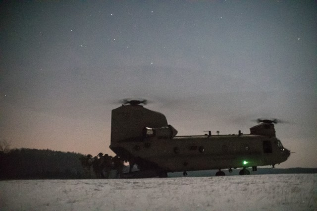 U.S. Army Rangers assigned to the 75th Ranger Regiment load a 12th Combat Aviation Brigade CH-47 Chinook helicopter at the conclusion of training at the Joint Multinational Readiness Center in Hohenfels, Germany, February 23, 2018. Rangers spent 72 hours training at JMRC as the culmination of a winter warfare training, which included training with the German military.