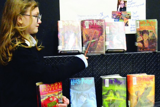 "VICENZA, Italy - Fifth-grader Georgia Hess, dressed up as Harry Potter, points her favorite book ""Harry Potter and the Chamber of Secrets"" by J. K. Rowling. Hess said she picked Rowling because her stories are inspiring."