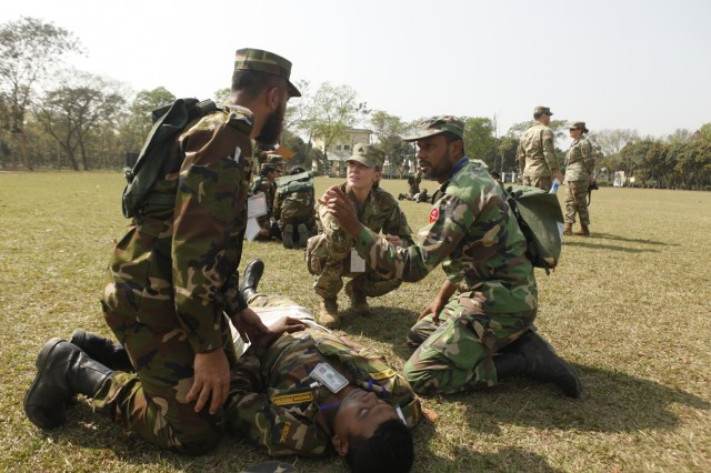 U.S. Army National Guard Sgt. Amber Demott, a medic with the Idaho Army National Guard Medical Detachment, discusses medical techniques with Bangladesh Army soldiers as they practice giving medical aid to role-players during a simulated mass casualty training event as part of Exercise Shanti Doot 4 in Bangladesh. Shanti Doot 4 is a multinational United Nations peacekeeping exercise with more than 1,000 participants from more than 30 countries designed to provide pre-deployment training to U.N. partner countries in preparation for real-world peacekeeping operations.