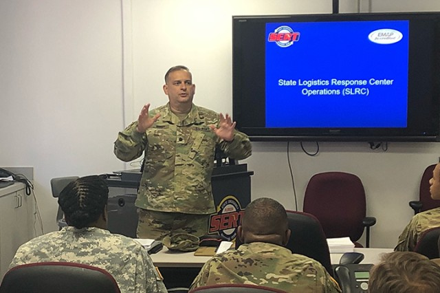 Lt. Col. Ricardo Roig, commander of the 930th Digital Liaison Detachment, discusses the role played by the Florida National Guard in the operations of the State Logistics Response Center (SLRC) during a training exercise April 7, 2018, with units from the 50th Regional Support Group in Orlando.