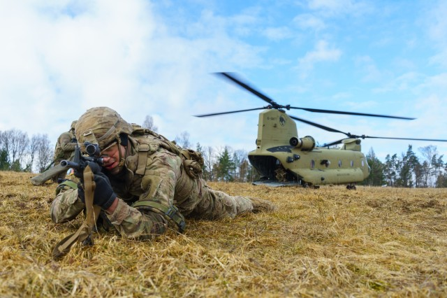 A cannon crewmember with Battery B, Field Artillery Squadron, 2nd Cavalry Regiment, pulls security after exiting a CH-47 Chinook helicopter with Company B, 2nd General Support Aviation Battalion, 227th Aviation Regiment, 1st Combat Aviation Brigade, at the Grafenwoehr Training Area in Germany, Mar. 8, 2018.