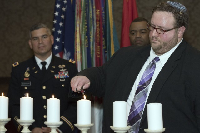 Rabbi Eric Mollo lights a candle symbolizing 'the old and young, for countless good-byes filled will emotion' during Fort Jackson's Day of Remembrance Observance April 10 at the NCO Club.