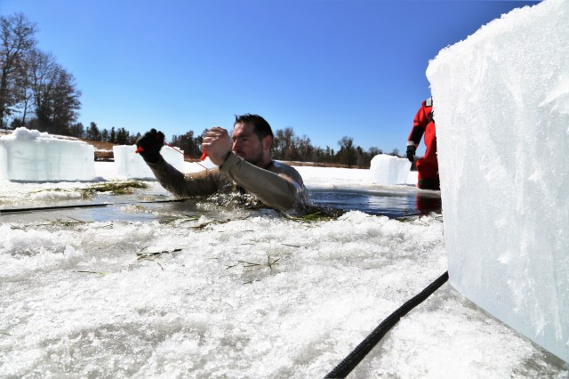A student in Cold-Weather Operations Course (CWOC) Class 18-06 participates in cold-water immersion training March 14, 2018, at Fort McCoy, Wis. In addition to cold-water immersion, CWOC students are trained on a variety of cold-weather subjects, including snowshoe training and skiing as well as how to use ahkio sleds and other gear. Training also focuses on terrain and weather analysis, risk management, cold-weather clothing, developing winter fighting positions in the field, camouflage and concealment, and numerous other areas that are important to know in order to survive and operate in a cold-weather environment. The training is coordinated through the Directorate of Plans, Training, Mobilization and Security at Fort McCoy. (U.S. Army Photo by Scott T. Sturkol, Public Affairs Office, Fort McCoy, Wis.)