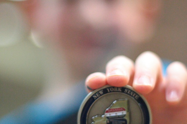 Col. Shane Morgan, 1st Brigade Combat Team commander, presents children with a commemorative 4-H Military Challenge Coin at the conclusion of the Month of the Military Child event at the 10th Mountain Division and Fort Drum Museum on April 7. (Photo by Kent Bolke, 10th Mountain Division and Fort Drum Museum)