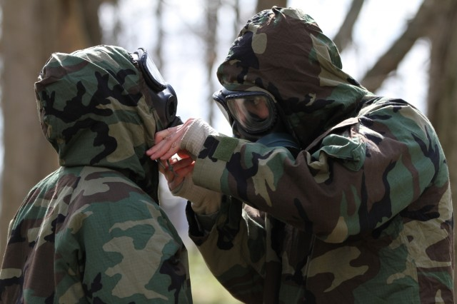 Two soldiers assist each other in securing their Mission Oriented Protective Posture level 4 gear during a timed event at the Chemical, Biological, Radiological, and Nuclear defense response train the trainers event on Camp Atterbury Maneuver Training Center, April 7, 2018. The three day training covered how to respond to CBRNE attacks, perform decontamination, identifying and report CBRNE attacks, and setting up gas chamber training.