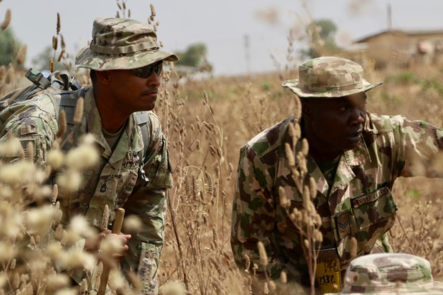 A U.S. soldier, left, coaches his Nigerian counterpart during a training exercise at a remote military compound located about 145 miles north of Abuja, Nigeria, Feb. 14, 2018. Twelve U.S. Soldiers provided tactics and training instruction to about 200 Nigerian army soldiers from the 26th Infantry Battalion. The seven-week training course includes instruction on reacting to an improvised explosive device, reacting to an ambush, securing an objective, operations planning and more. Army photo by Capt. James Sheehan